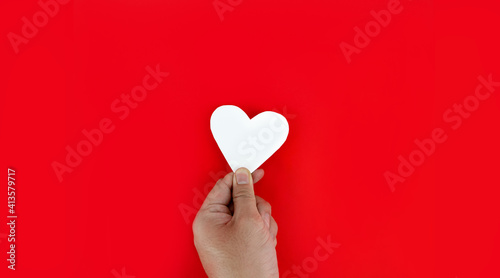 Canvas Print Hand holding a white heart on a red background The meaning of true love is the best wishes for those whom they love, the joy that the loved ones are happy with
