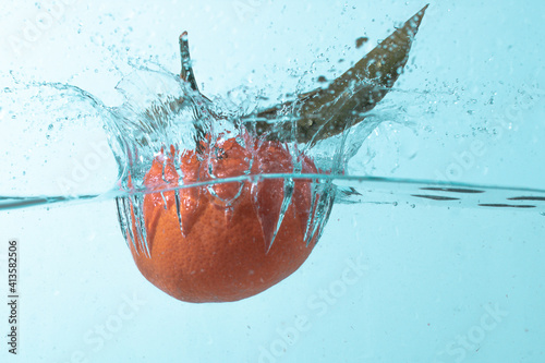 Closeup of a ripe tangerine falling into the water against a blue background Fototapet
