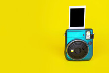 Instant Camera On Yellow Background With Snapshot Of Photo.