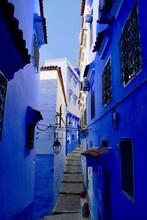 Narrow Alley Amidst Buildings Against Blue Sky