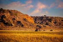 Oil Well Pump Jack In Red Earth Western Oklahoma At Golden Hour With Early Sunset Sky And Bluffs In Background.