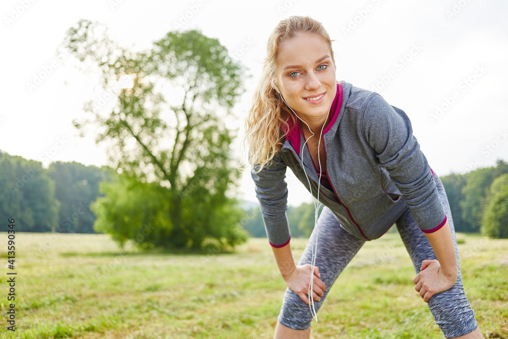 Fototapeta Portrait Of Smiling Young Woman Exercising On Field