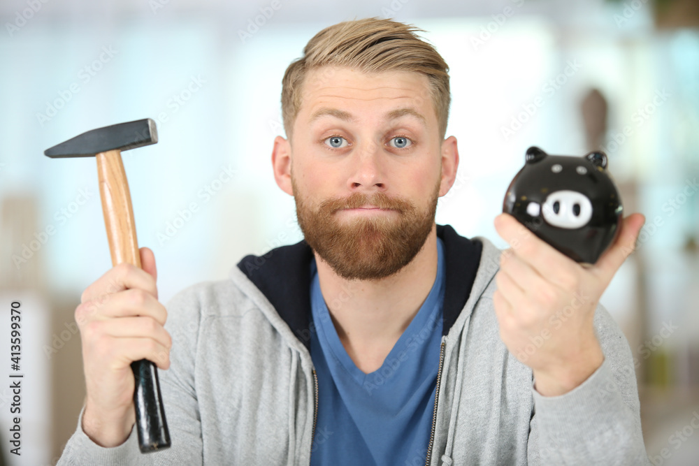 Fototapeta man about to break a ceramic piggy-bank with hammer