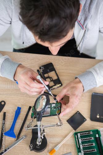Fototapeta close-up of a human hand repairing smartphone with screwdriver obraz