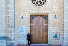Tourist With Cap Posing Next To A Door Of A Church In Malta