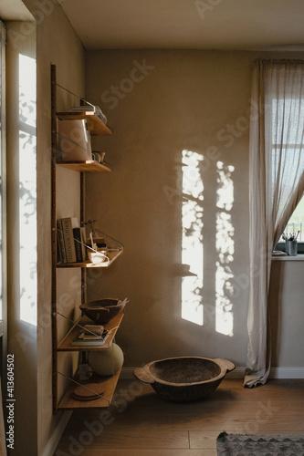 Lichtspiel in einem Wohnraum mit Regal und Gardinen und Fenster in skandinavischem Design
