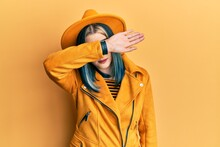 Young Modern Girl Wearing Yellow Hat And Leather Jacket Covering Eyes With Arm, Looking Serious And Sad. Sightless, Hiding And Rejection Concept