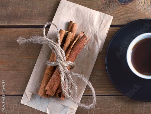 Cinnamon sticks lie on paper on a wooden table Fotobehang