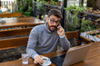 Handsome man with glasses working on laptop and talking on smartphone in the coffee bar.