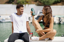 Young Sporting Couple Hydrate Themselves With Water In Metal Cans While Taking A Break After Sport.