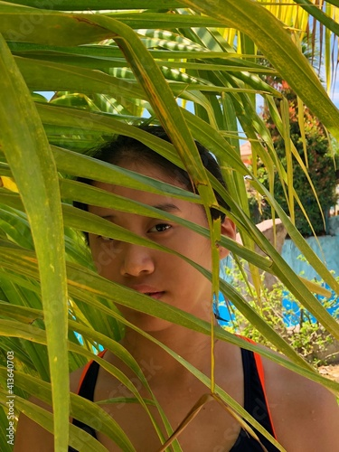 Fototapeta Portrait Of Girl Sen Through Palm Leaves obraz