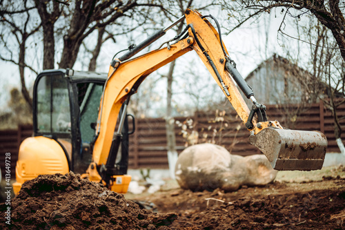 Fototapeta Landscaping works with mini excavator at home construction site. Terrain works obraz