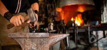 The Blacksmith Forging The Molten Metal On Anvil In Smithy. Blacksmith At The Workshop. Working Metal With Hammer And Tools In Forge