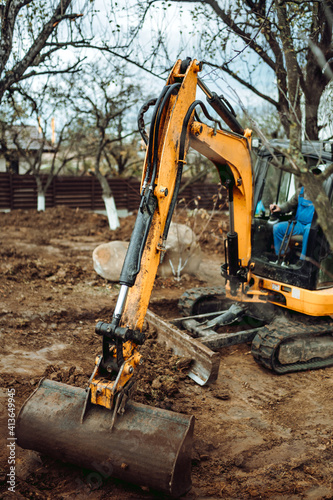Fototapeta Close up of industrial mini excavator scoop moving earth and doing landscaping works. obraz