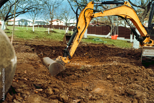 Fototapeta Landscaping works in the home garden at construction site with mini yellow excavator obraz