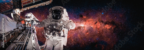 Fototapeta Astronaut spaceman do spacewalk while working for space station in outer space