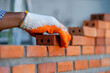 Bricklayer industrial worker installing brick masonry on exterio