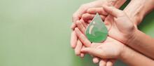 Hands Holding Paper Cut Green Oil Drop, CSR, Alternative Biofuel Renewable Green Energy Concept