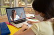 Caucasian schoolgirl wearing face mask and using laptop on video call with female teacher