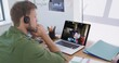 Caucasian man using laptop and phone headset on video call with male colleague