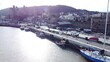 Idyllic Conwy castle and harbour fishing townscape boats on coastal waterfront aerial low angle reverse right