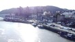 Idyllic Conwy castle and harbour fishing town boats on coastal waterfront aerial rising backwards reveal