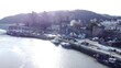 Idyllic Conwy castle and harbour fishing town boats on coastal waterfront aerial lowering to water below