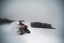 Friends Riding Snowmobile On Field Against Sky