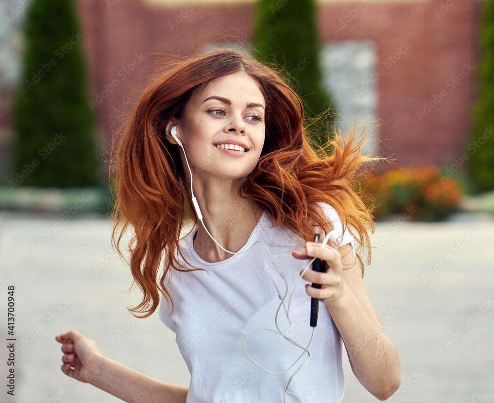 Fototapeta redhead woman outdoors walk headphones fun music