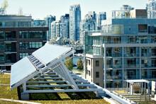 Solar Panel On Field By Buildings In City