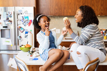 Playful Mother Eating Cupcakes With Daughter While Sitting On Kitchen Island