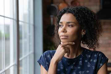Fototapeta na wymiar Close up thoughtful African American woman looking out window to aside, touching chin, dreamy young female lost in thoughts, planning, visualizing future, businesswoman thinking, making decision