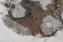 Stream Of Water In The Cold Season. Snow And Ice. Brown Bottom.