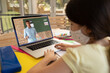 Female student wearing face mask having a video call with male teacher on laptop at school