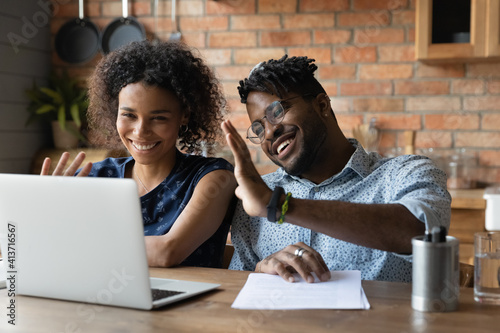 Obraz na plátně Close up happy African American couple making video call to friends or relatives