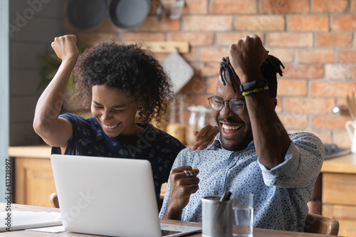 Fototapeta Close up excited African American couple celebrating success, using laptop, overjoyed wife and husband received good news in email, online lottery win or approved mortgage loan, showing yes gesture obraz