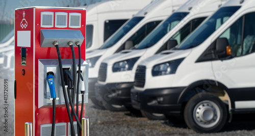 Fotografía Electric vehicles charging station on a background of a row of vans