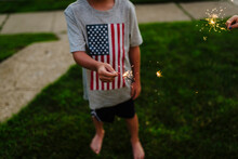 Low Section Of Boy Holding Sparkler While Standing On Field