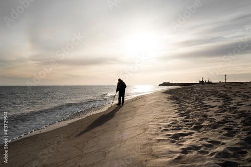 Obraz Szerokie ujęcie pod światło samotnego mężczyzny spacerującego brzegiem morza - fototapety do salonu