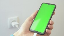 Charging Charge Mobile Phone, Smartphone. Man Holds A Cell Phone In His Hand On A Background Of Walls And Sockets. Connecting The Charger USB C. Charg Device Process. Green Screen.