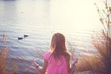 Rear View Of Girl Meditating While Sitting By Lake