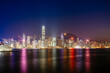 Victoria harbour against illuminated Two International Finance Center and buildings in city at night