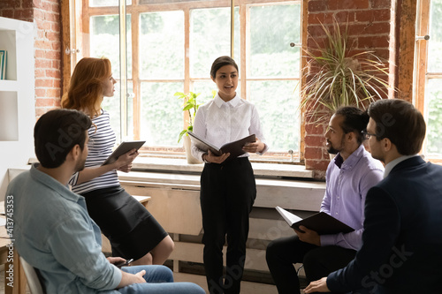 Fototapeta Confident young Indian businesswoman lead meeting with multiethnic colleagues in office. Millennial mixed race ethnicity female leader talk discuss business project with employees at briefing. obraz na płótnie