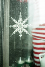 Child Decorating And Hanging Christmas Stars On Window