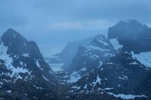 View Through Mountain Pass Towards Distant Village Of Reine From Summit Of Narvtind Mountain Peak, Moskenesøy, Lofoten Islands, Norway