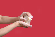 Woman Washing Hands With Soap On A Red Background