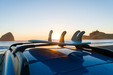 Surfboard On Car Roof At Beach Against Clear Sky During Sunset