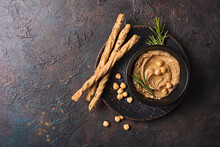 Bowl Of Tasty Traditional Homemade Hummus With Rosemary And Bread Sticks
