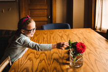Little Girl Smiles While Reaching For Flowers In Vase On Table