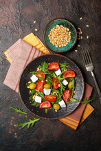 Healthy Vegetarian Salad With Fresh Arugula, Cherry Tomatoes, Soft Cheese, Olives And Pine Nuts